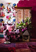 Floral sofa, old birdcage, patchwork rug in various shades of red, bouquet, cupboard with louver doors and floral wall hanging