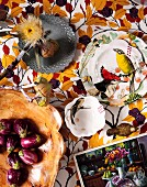 Various dishes made from different materials, some painted with bird motifs and dried flowers on fabric with pattern of autumn leaves