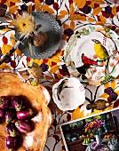Verschiedene Schalen aus verschiedenen Materialien, teilweise bemalt mit Vogelmotiven und getrocknete Blumen auf Stoff mit Herbstlaub Motiv