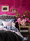 Double bed with button-tufted headboard and white, blue and grey bed linen next to bouquet on bedside table against purple-painted wall