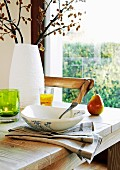 Bowl on linen napkin and white vase of flowering branches on wooden table