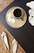 Coffee cup on saucer on black tray next to ladies' shoes on sisal rug