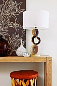 Table lamp with artistic base made from slices of branch and white lampshade on wooden table