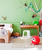Modern wooden bed next to writing desk and white plastic stool below stylised tree made from wooden planks on green wall; red space hopper on rug in foreground