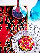Artistic metal dish of red and yellow flowers and two shiny vases on rug with red and black pattern