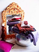 Mirror with artistically carved frame and spherical silver vase decorated with folded scarves and cushion
