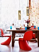 Red Panton chairs around solid wooden table set with blue glasses in front of delicate floral curtains