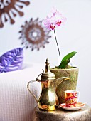 Red china cup, shiny brass jug and pink orchid in gold-coloured pot