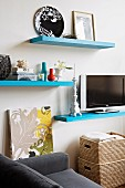 Flatscreen TV on pale blue floating shelf amongst other shelves and home accessories in living area