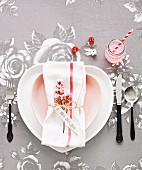 Romantic place setting with rose-patterned tablecloth, heart-shaped plate and sprig of pink flowers