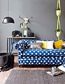 Blue and white polka-dot sofa in front of console table against grey wall and yellow macrame plant hanger