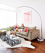 Arc lamp, woman sitting on sofa and black and white patterned floor cushions under transparent coffee table in comfortable, sunny lounge area