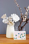 White-painted artificial flowers in simple vase and postcard in front of flowering branch in glass vase against mauve background