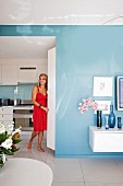 Interior painted pale blue with partially visible floating sideboard with collection of blue vases; woman wearing red dress in open doorway