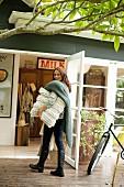 Junge Frau mit Strickkissen und Wolldecke bepackt vor offener Glastür mit Blick auf Raum im Vintagelook