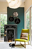 Hand-crafted, stylised open fire made from wooden board, blackboard paint, chalk and fairy lights in comfortable seating area with green chair and embroidery frames on wall