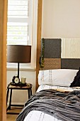 Bed headboard hand-crafted from patchwork knitted squares covering wooden board