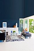 Elegant living room with dark blue wall, woman reading in front of an open terrace door