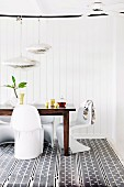 Dining area with white panton chairs and wooden table on patterned carpet in front of white wall covering