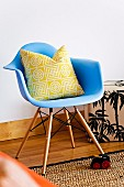 Graphically patterned pillow on light blue shell chair