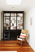 Cozy reading area with rocking chair and black retro bookcase
