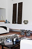White lowboard with vases and carved, Indian wooden panels, in front of it black and white stools, zebra fur and coffee table in a bright living room