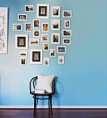 Thonet chair with white cushions below collection of pictures on blue wall
