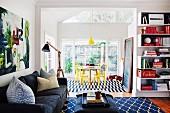 Offenes Wohnen - neben schwarzer Polstercouch Stehleuchte mit Holzgestell und Couchtisch auf gemustertem Teppich, im Hintergrund Essplatz mit gelb lackierten Thonetstühlen in hellem Anbau