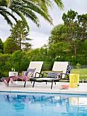 Zwei Sonnenliegen mit gemusterten Kissen an Pool vor Glasbrüstung und Gartenblick