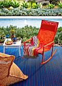 Orangefarbener Schaukelstuhl auf blauemTeppich neben Beistelltisch mit Cocktailgläsern vor Pool