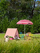 Tent-shaped wooden frame covered with patterned fabric next to colorful garden chairs and a red and white parasol