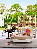 Round designer sofa with headphones in front of a wooden screen on the terrace next to a women's bike and glass fire