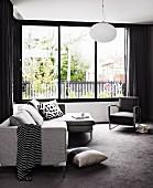 Wohnzimmer mit Sofagarnitur in puristischen Grautönen am Fensterfront