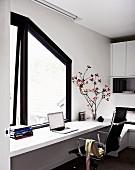 weiße durchgehende Schreibplatte vor dunkel gerahmtem Fenster mit Dachschrägung, ergänzt mit Eames Stuhl