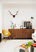 Fifties-style, engineered-wood shell chairs, pictures and coloured bottles on top of 70s sideboard and stag's antlers on wall