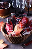 Basket of small bottles of drink decorated with painted autumn leaves