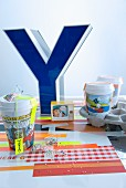 Large, blue, ornamental letter on colourful place mat and paper cups with comic-page print