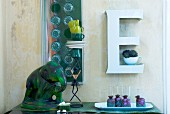 White, ornamental letter used as wall bracket, green elephant ornament and artistically stacked crockery on sideboard