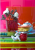 Colourful still-life arrangement with red Aalto glass vase and elegant teapot on glass surfaces in various colours