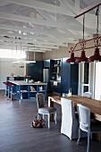 Esstisch mit verschiedenen Polsterstühlen unter roter Vintage Hängeleuchte und Küchenbereich im Hintergrund
