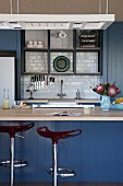 Blue-painted kitchen counter with designer bar stools; white tiled splashback in fitted kitchen in background