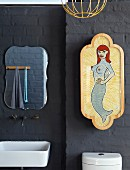 Grey-painted brick wall with wall-mounted tap fittings, sink, curved mirror and framed picture of mermaid
