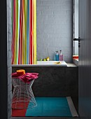 Colourful striped shower curtain, bathtub and wire-framed stool in grey-painted bathroom