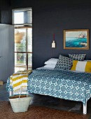 Double bed with blue and white patterned bedspread against brick wall painted dark grey and view into bright hallway