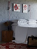 Double bed below red and white floral paintings and innovative sconce lamps on brick wall painted dark grey