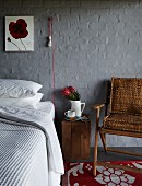 Innovative sconce lamp on grey-painted brick wall above bed with wooden crate used as bedside table and armchair
