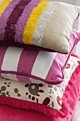Stack of decorative pillows in assorted pink and purple fabrics