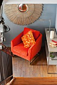 Looking down from a stairway at an orange, velvet armchair with plush cushions and decorative 'sun' with stylized rays