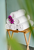 Rolled bath towels decorated with flowers on a small, wooden table