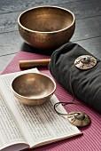 Tibetan bowls, cymbals and an open book in sanskrit on a pink yoga mat